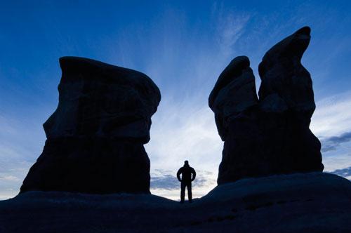Man standing between two sandstone features in Devil's Garden, Utah.