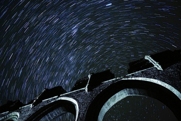 Star trails with the ruin of a priory in the foreground