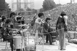 A band plays on stage at the festival. Wolman's images are notable for the balance between images of the stage and of the crowd. Seeing them together like this gives real scale to the event