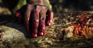 A ranger's bloody hand rests on an ivory tusk during an anti-poaching mission in KwaZulu-Natal, South Africa © Britta Jaschinski / Photographers Against Wildlife Crime(TM)