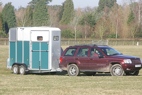 A 4x4 towing a two-horse trailer across a field
