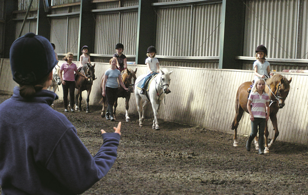 Riding school lesson in an indoor arena with children leading ponies