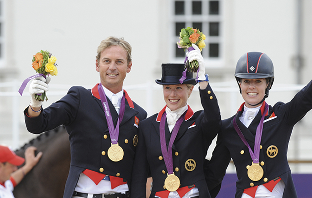 British team on the podium receiving thier medals. L to R Carl Hester, Laura Bechtolsheimer, Charlotte Dujardin