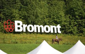 A horse and his cavalier pass in front of the Bromont sign at Bromont Olympic Horse Park