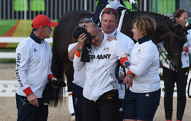 Groom Robbie Sanderson being helped from the team dressage medal ceremony