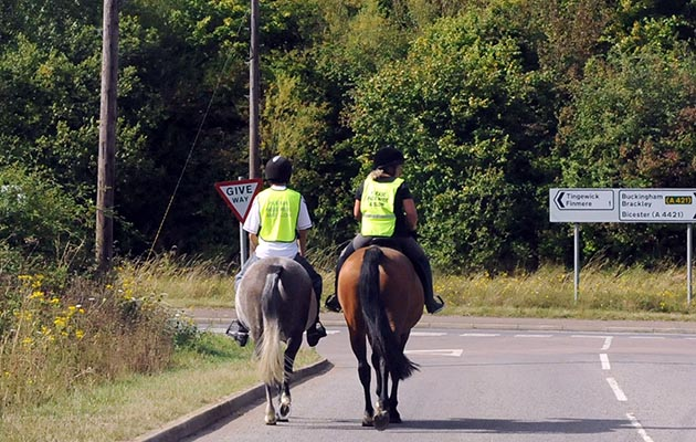 C7H3AN Two young horse riders riding on a main road at a road junction