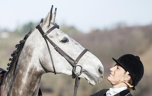 Harriet Fairhurst and horse Hazel. show cover, kissing horse, bonding with horse,cuddle,rosette,showing head,grey horse,hunter