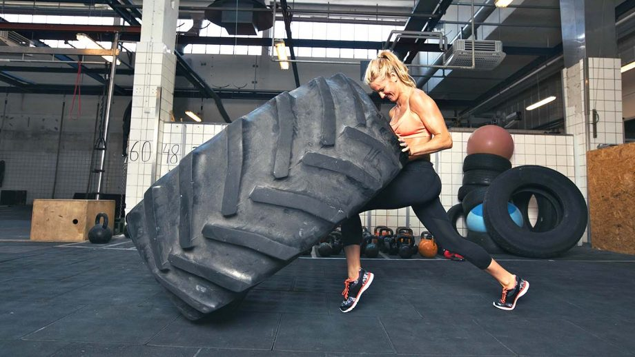 E4RRGN Fit female athlete working out with a huge tire, turning and flipping in the gym. Crossfit woman exercising with big tire.