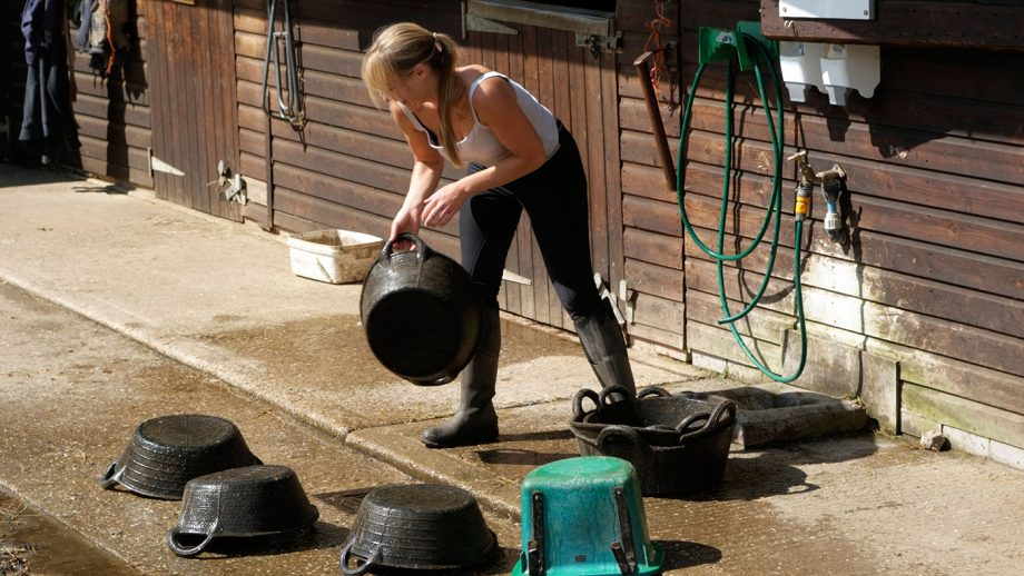 B1D39K Woman washing and cleaning horse feed bowls and rubber buckets. Image shot 06/2008. Exact date unknown.