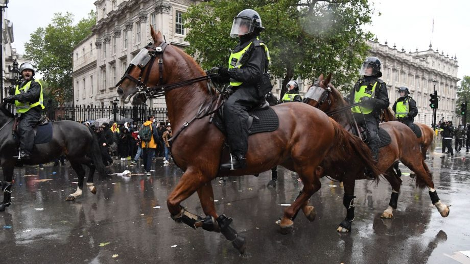Mounted police officers charge their horses along Whitehall, past the entrance to Downing Street, in an attempt to disperse protestors gathered in central London on June 6, 2020, during a demonstration to show solidarity with the Black Lives Matter movement in the wake of the killing of George Floyd, an unarmed black man who died after a police officer knelt on his neck in Minneapolis. - The United States braced Friday for massive weekend protests against racism and police brutality, as outrage soared over the latest law enforcement abuses against demonstrators that were caught on camera. With protests over last week's police killing of George Floyd, an unarmed black man, surging into a second weekend, President Donald Trump sparked fresh controversy by saying it was a