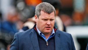 British racing has banned Gordon Elliott-trained runners, pending an investigation into a photo of the trainer sitting on a dead horse