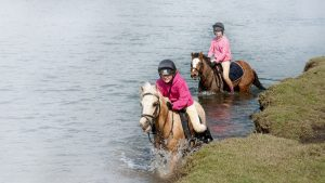 CNKKBW Pony riders crossing the River Ewenny at Ogmore in the Vale of Glamorgan S Wales UK. Image shot 04/2012. Exact date unknown.