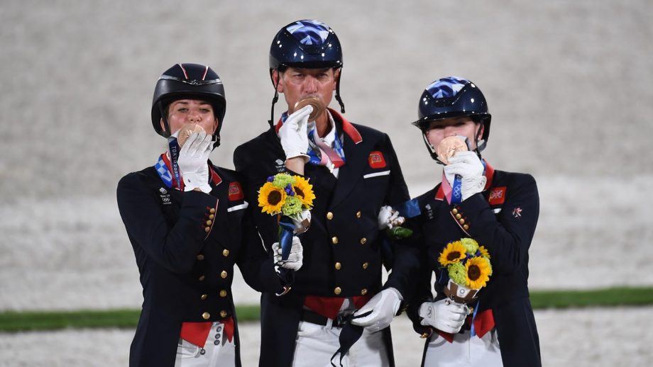 British dressage team kiss their bronze medals while standing on the podium in Tokyo