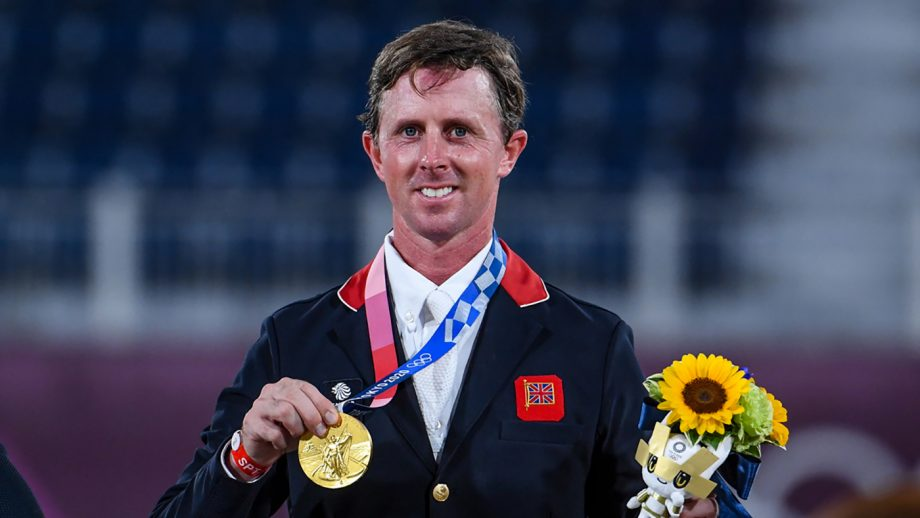 Ben Maher holds up his gold medal after winning the Olympic showjumping individual final