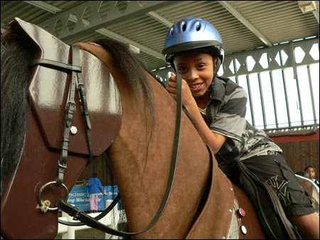 A local child tries out the mechanical horse at the interactive launch of the Equine Health and Welfare Strategy