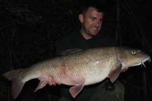 Simon Cook admires his giant Thames barbel.
