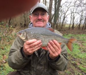 Joe Froggett, partially obscured by the photographer's thumb, shows his huge Hampshire Avon roach.