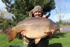 Craig McEvoy displays his impressive 58 lb carp at The Avenue.