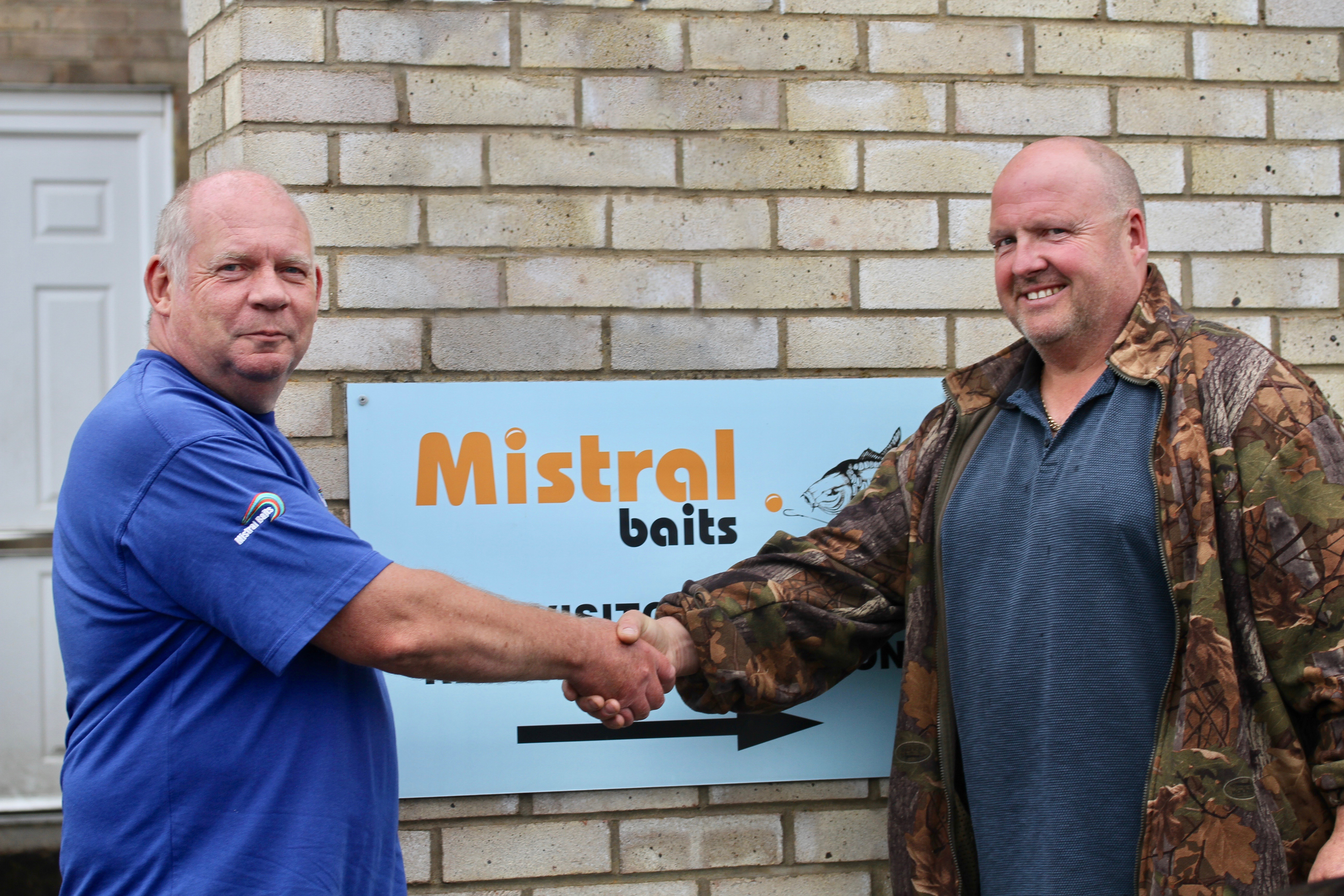 Jim Shelley (right) shakes on a deal with Allan Parbery at Mistral Baits.