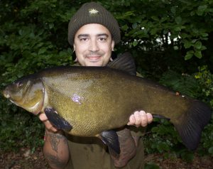 Matthew Fernandez shows his giant 12 lb 8 oz tench.