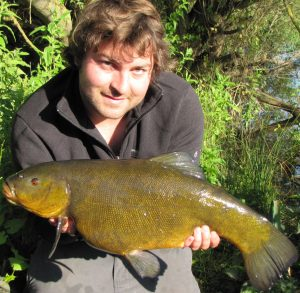 Jamie Cook, seen with a tench, is an all round angler with an impressive list of PBs.