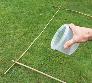 Weigh the appropriate amount of products, make a 1m sq measure with canes, lay it on the lawn and sprinkle evenly over the area. Note coverage, and spread the rest evenly over the whole area at a similar density