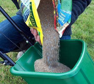 CNAXHE Pouring lawn fertilizer and weedkiller into a rotary lawn feed spreader
