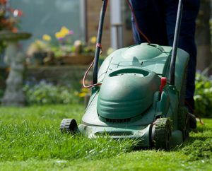 CP43B7 Gradener mowing the lawn in april. Cutting the grass. Gardening jobs