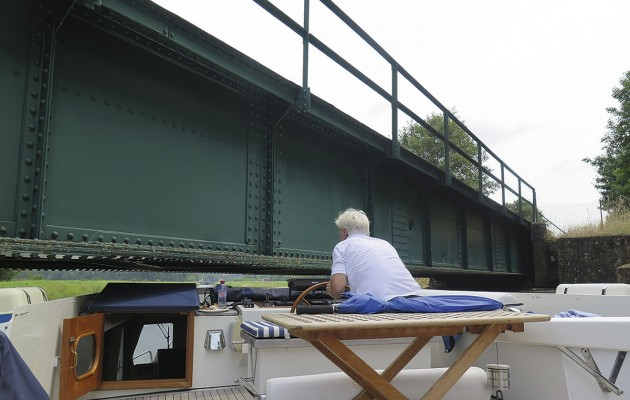 Howard Walker squeezes under a low bridge in the French canal system