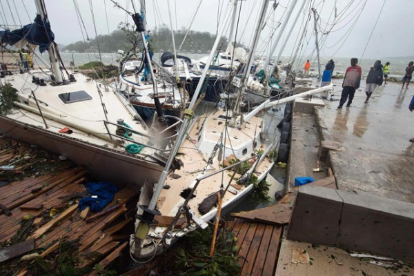 Local residents look at damaged boats against a jetty in Port Vila. Picture credit: UNICEF Pacific