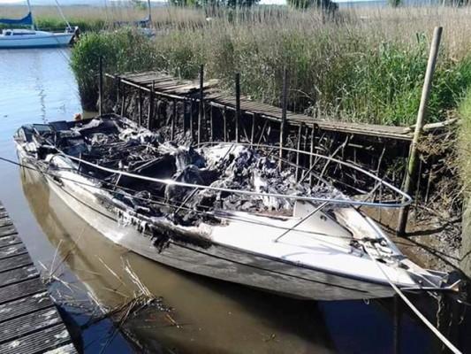 The fire-damaged boat moored near Swineham Point, Wareham