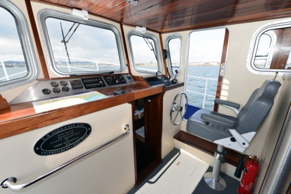 Tug Yacht 33 - The little ship theme continued in the raised pilot house with its pedestal captain's chair and vertical wheel
