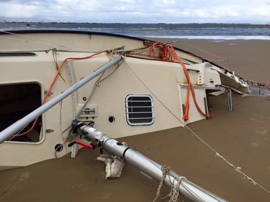 A yacht abandoned by a Russian sailor who was rescued in storms off the coast of Norfolk is still beached at Scroby Sands - three months later. Credit: Caister Lifeboat