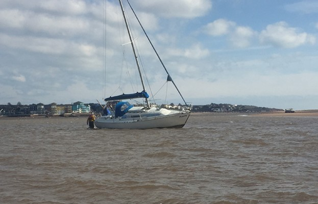 Exmouth RNLI crew member assists one of two stricken yachts in the Exe estuary. Credit: Exmouth RNLI