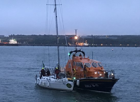 The yacht, with a fouled propeller, in an alongside tow with Angle RNLI's all weather lifeboat. Credit: Angle RNLI