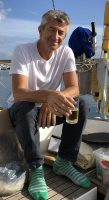 Golden Globe Race sailor Ertan Beskardes in a white tshirt and sipping a beer