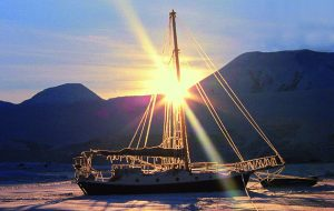 A Wylo yacht in ice with a rising sun in the background