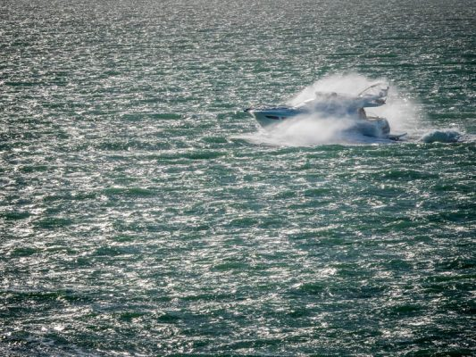 Power boat in stormy sea covered in spray