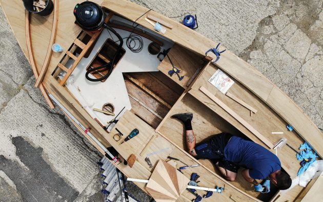 Much of the work during the summer has been done outside. This drone shot shows the teardrop shape of the hull, and how much room the cockpit offers by using Jesse Doyle's prone 6ft 2in figure as a benchmark. Photo: Jason Brodie-Brown