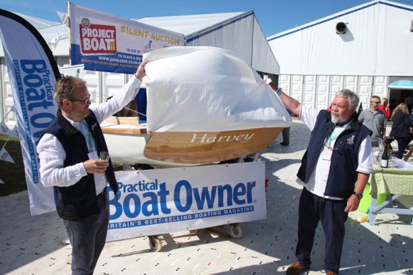 Practical Boat Owner editor Rob Melotti, left, and Oarsome Chance charity founder Paul O'Grady officially unveil the PBO Project Boat name plate on the stern of the kit built Secret 20 gaff cutter on stand E030A at Southampton Boat Show 2019