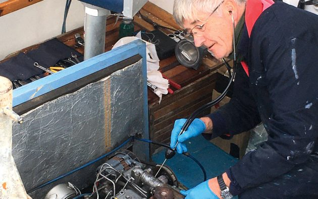Gilbert listens to the engine using a mechanic's stethoscope. Notice the bulb just below his right hand acts as amplifying box for the probe.