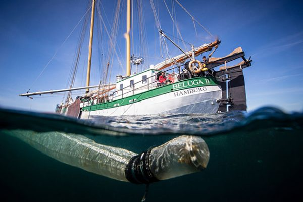 A can and a piece of plastic photographed under the water off Scotland with a green and white yacht behind it