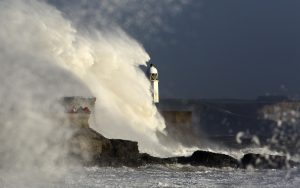 Waves hit a lighthouse during Storm Ophelia
