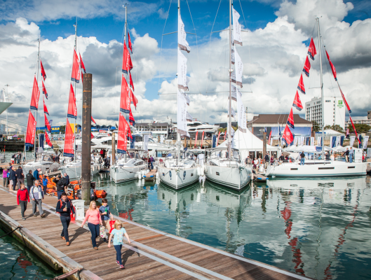 People walking on pontoons looks at boat at the Southampton Boat Show