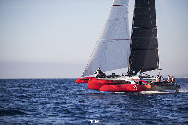 A red trimaran with black and white sails undergoing sea trials