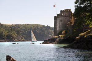 A yacht in full sail passing the castle on the River Dart