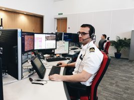 A coastguard officer in a white shirt sitting at a desk