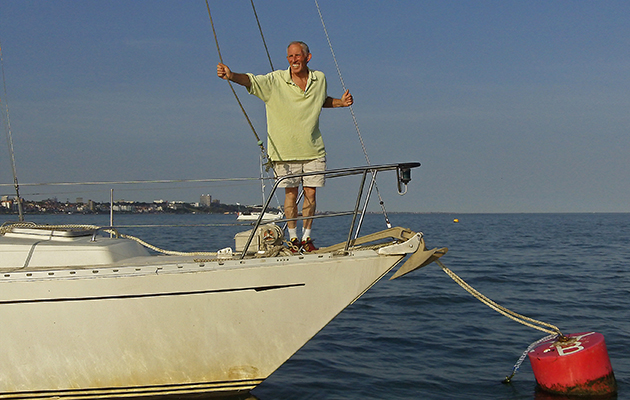 Robin Davie in a cream t-shirt on a bow of a boat