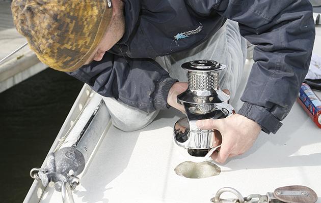 a man fitting an anchor wndlass on a yacht