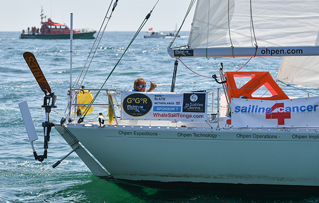 A skipper waves as he manoeuvres his yacht to the start line for the Golden Globe Race